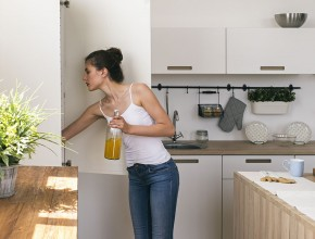 Side view of woman holding bottle of juice while looking in frid